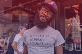"Man in front of outdoor bar wearing glasses, hat, and shirt that reads ""The Future is Female Ejaculation"" 